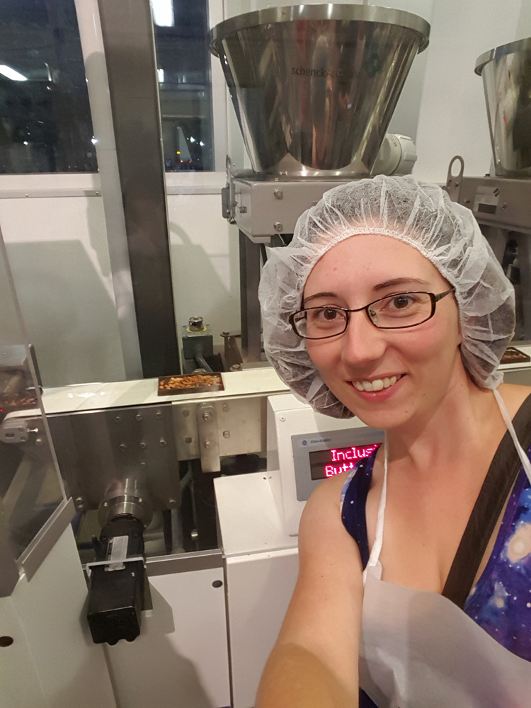 Woman posing in front of a chocolate bar making machine in Hershey, Pennsylvania