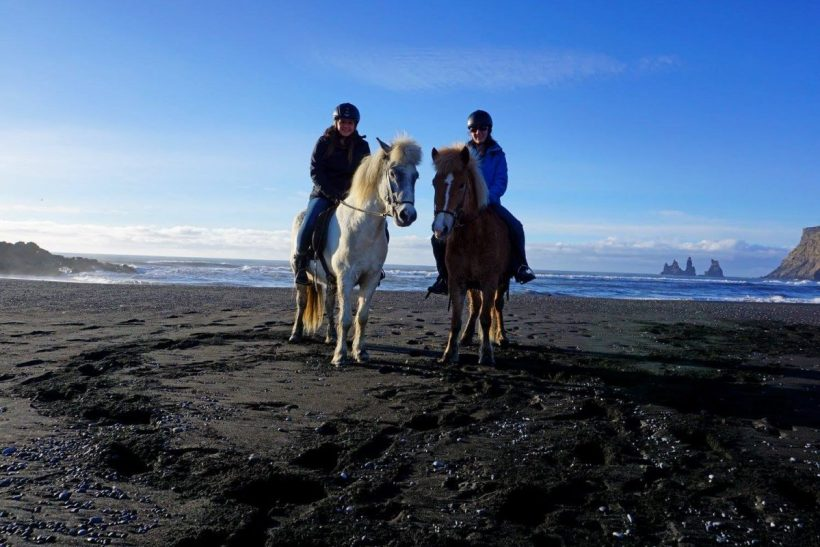 Horseback riding on a black sand beach in Iceland