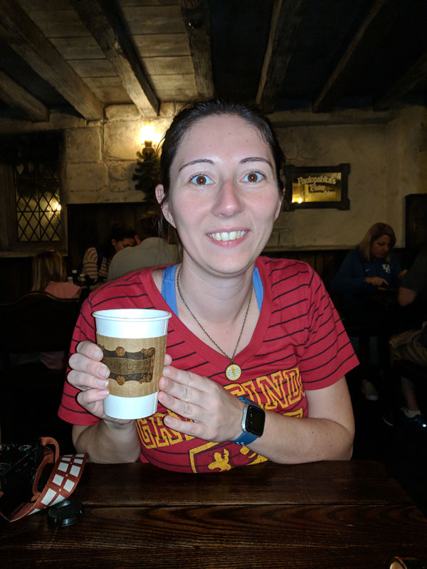 Woman holding a cup of hot butterbeer at Universal Studios Orlando