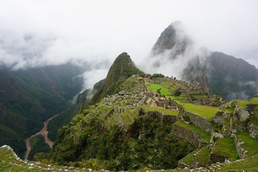 View of historic buildings at Machu Picchu with clouds in between