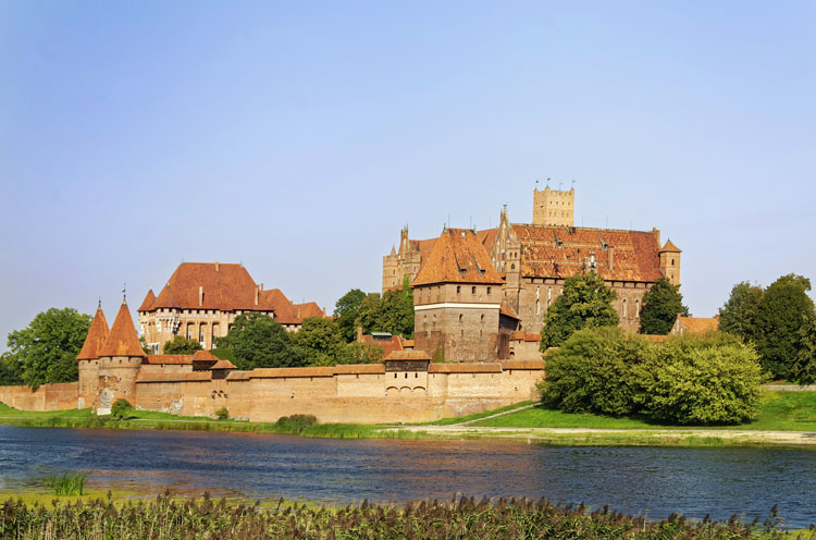 Large brick Malbork Castle along a river in Poland