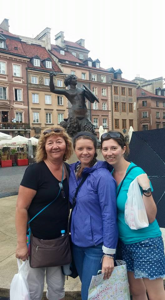 Three women in front of Warsaw's mermaid statue