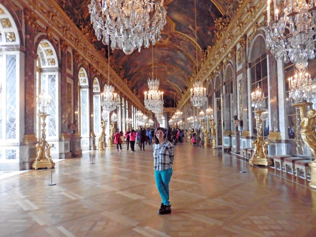Woman posing in the Hall of Mirrors at Versailles Palace in winter
