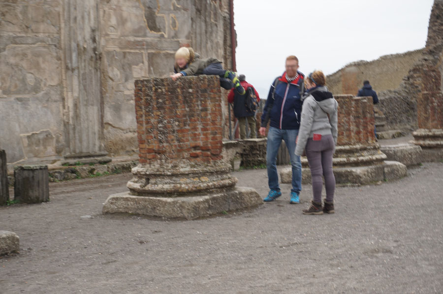 Child climbing on artifacts in the Pompeii ruins