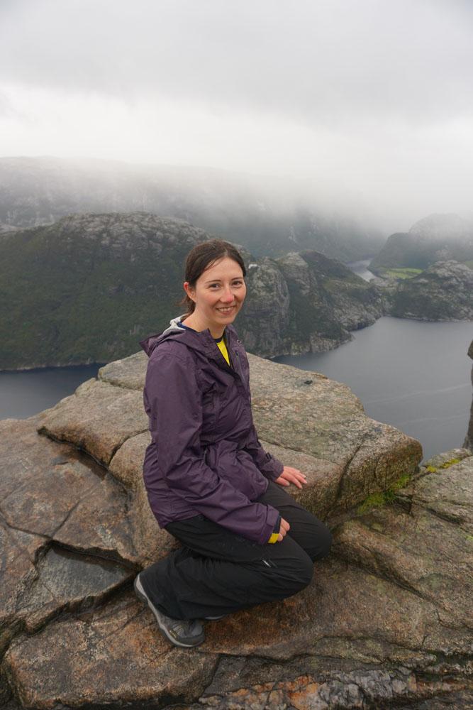 Woman sitting atop Preikestolen in fog