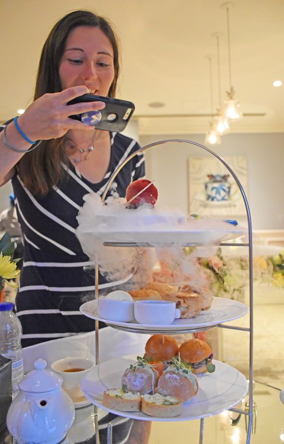 Woman photographing an afternoon tea serving tower.