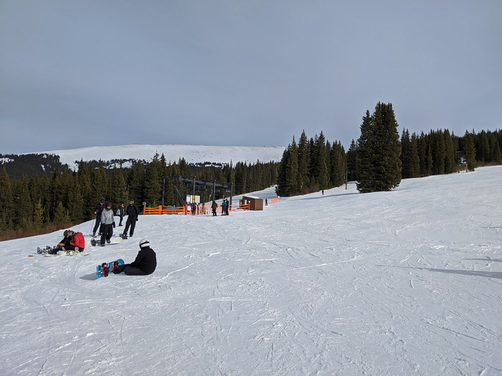 Snowboarders at the top of Cooper Mountain