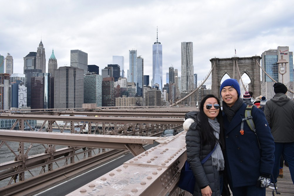 Couple posing on the Brooklyn Bridge in front of the Manhattan skyline