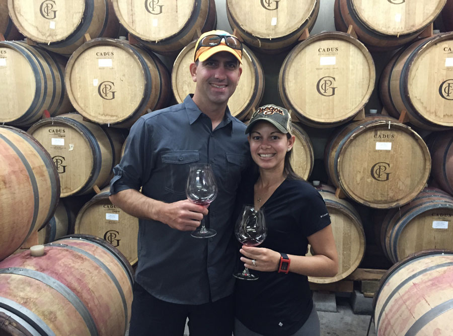 Man and woman posing with wine glasses in front of wine barrels