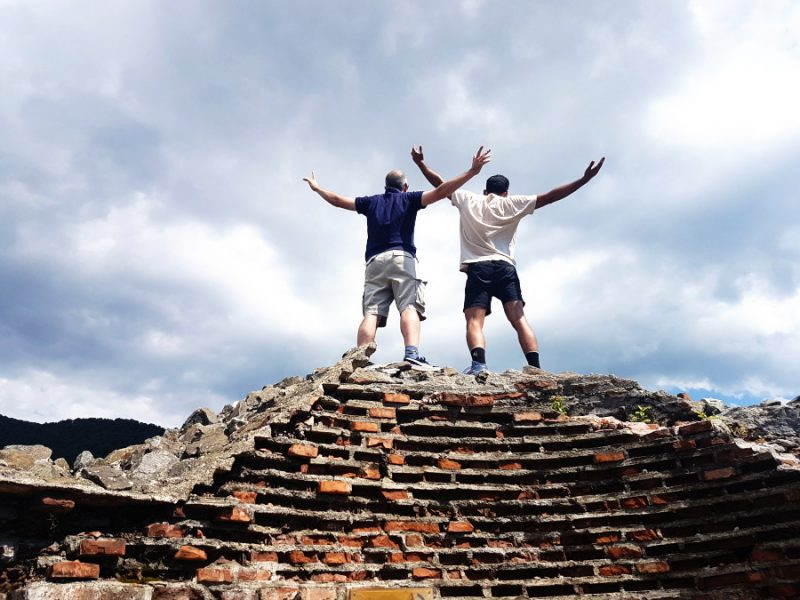 Two men seen from behind standing on a ruined brick structure