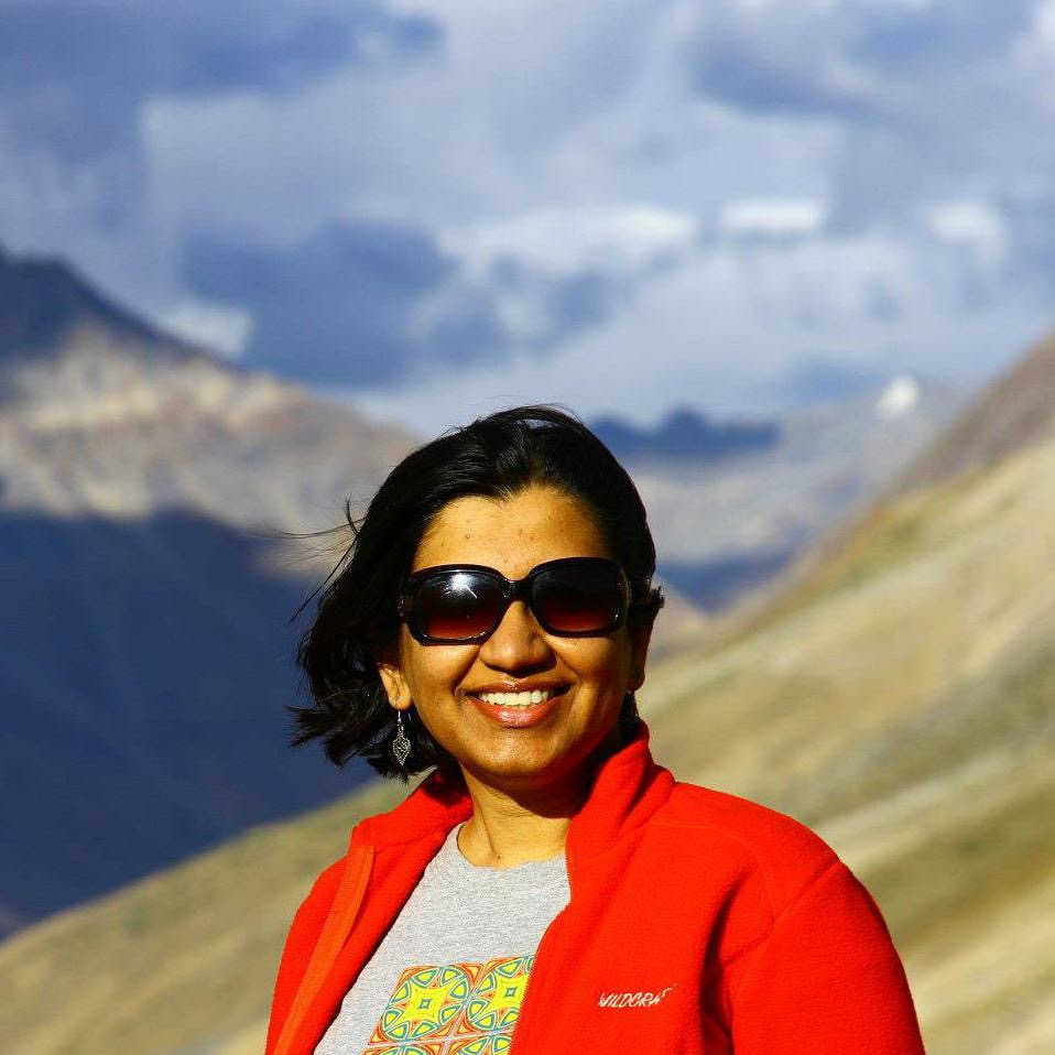 Neha Sharma the creator of the Nomadic Dreamz travel blog, standing in front of a mountain landscape, wearing sunglasses and a red jacket
