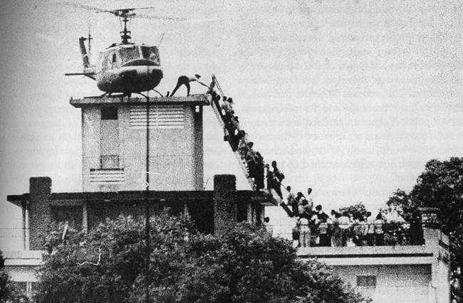 A helicopter sits on top of a building in Saigon evacuating south Vietnamese people who aided the US in the Vietnam War.