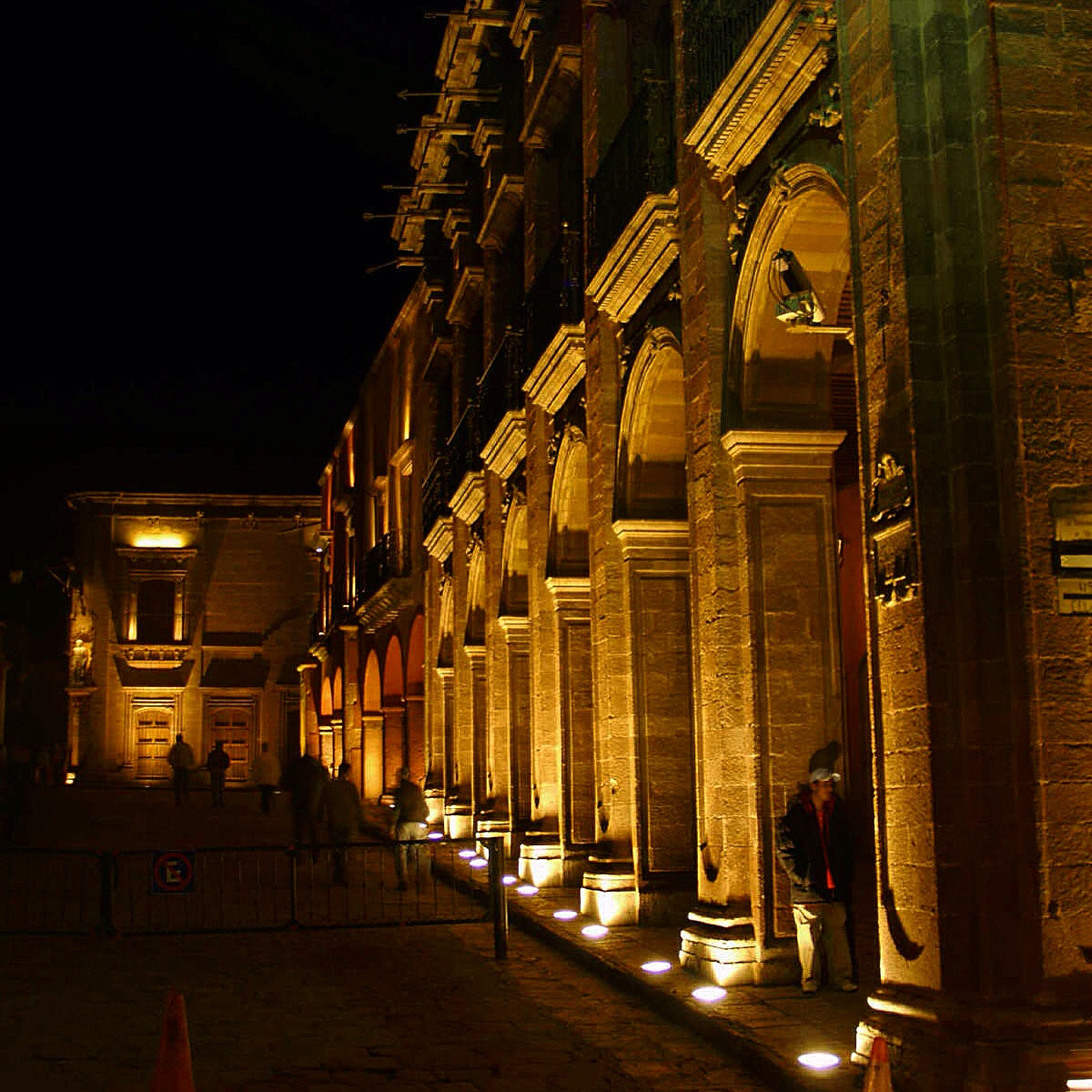 The portales in the main plaza of San Miguel lit up at night.