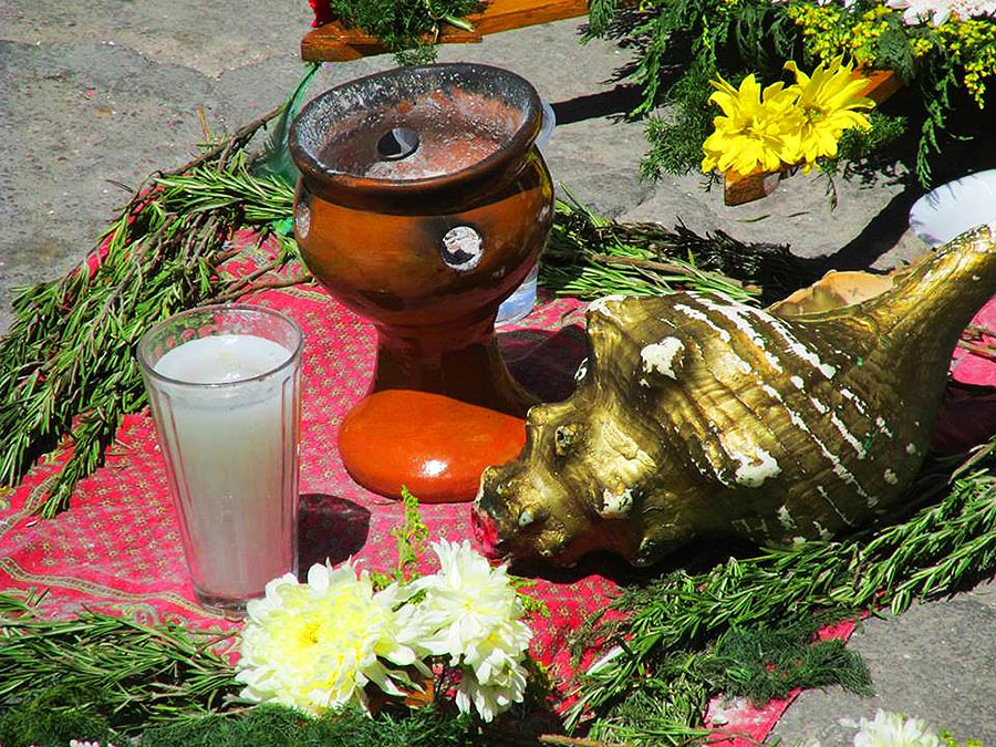Copal incense smoke rises from a burner beside a conch shell and candle--symbols of the conchero dancers' devotion