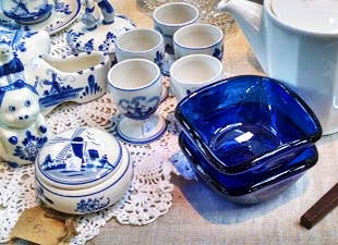 Blue-and-white Delft-style coffee service and cobalt blue glass bowls on a table.