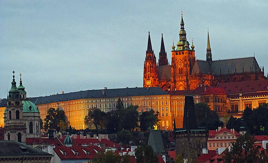 Prague castle lit by the setting sun at dusk.