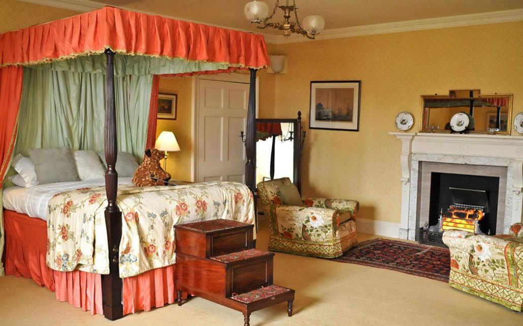 The lovely Ailsa Suite at Culzean, with its carved and canopied four-poster bed and wooden steps to get up into it.