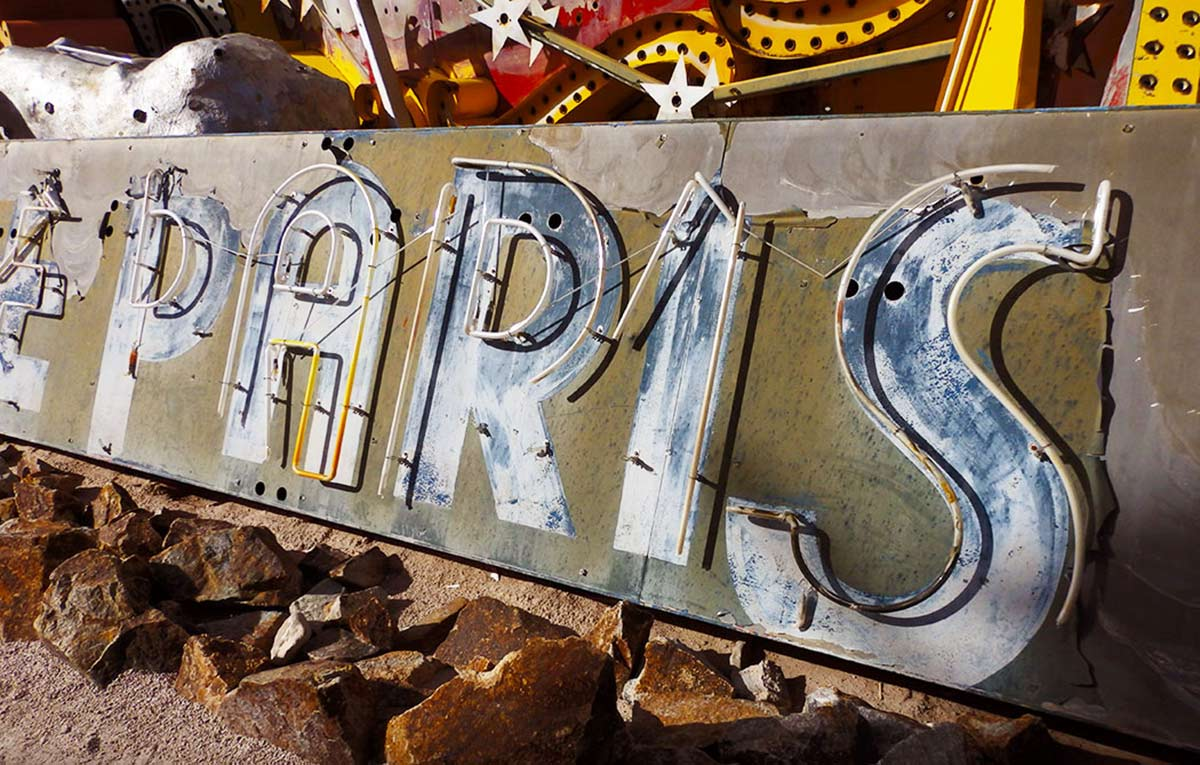 An old and faded neon sign for the original Paris casino in Las Vegas. At the Neon Boneyard of the Las Vegas Neon Museum.