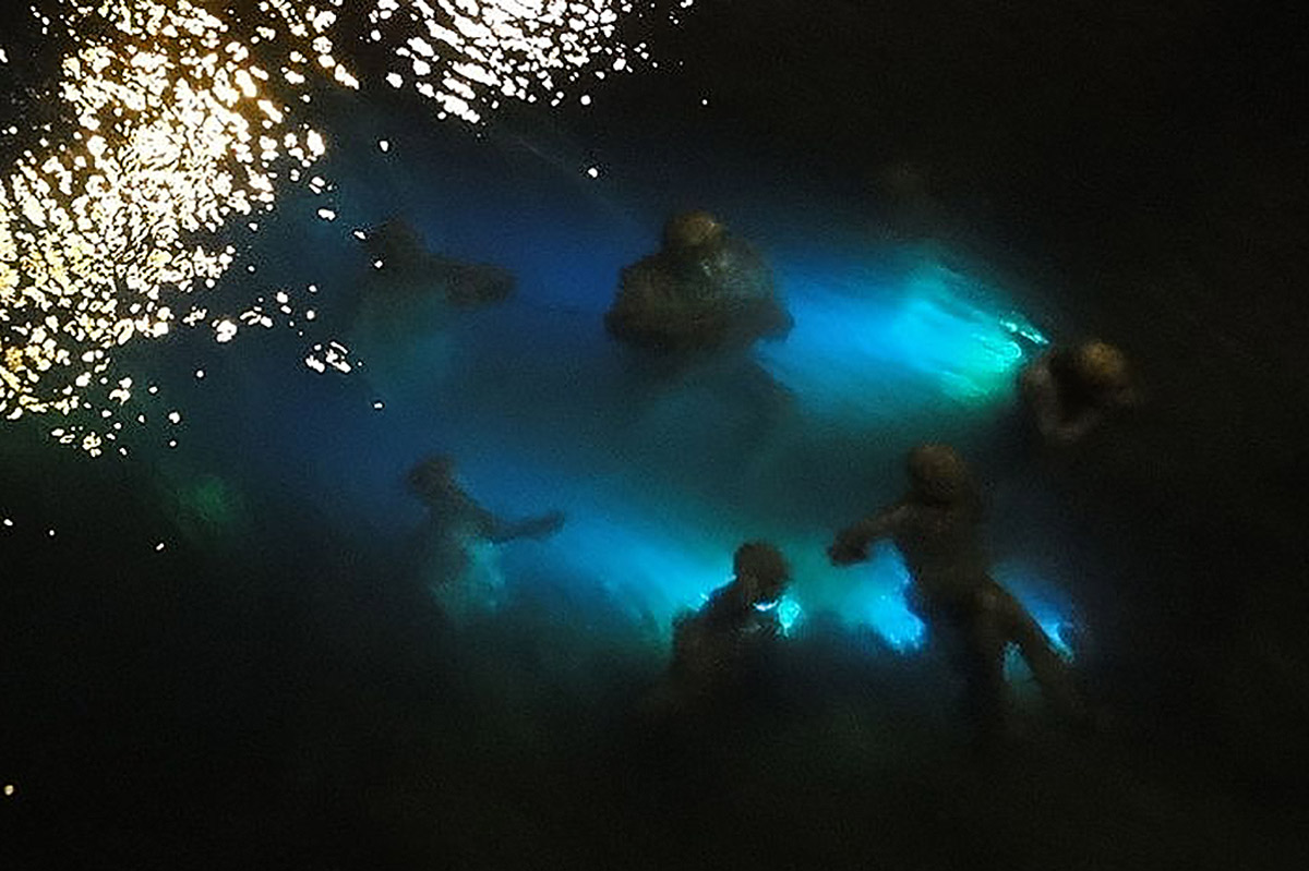 The figures of the sculpture Agnete and the Merman look ghostly in the glow of the underwater lights at night, seeming to move and keen with the undulating water.
