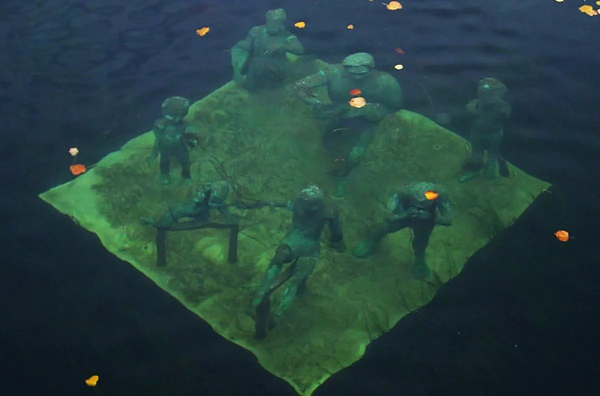 The grouping of seven bronze figures on a square bronze platform called Agnete and the Merman can be seen just below the surface of the blue-green water in the Slotsholm Canal next to the Højbro Bridge, in Copenhagen, Denmark.