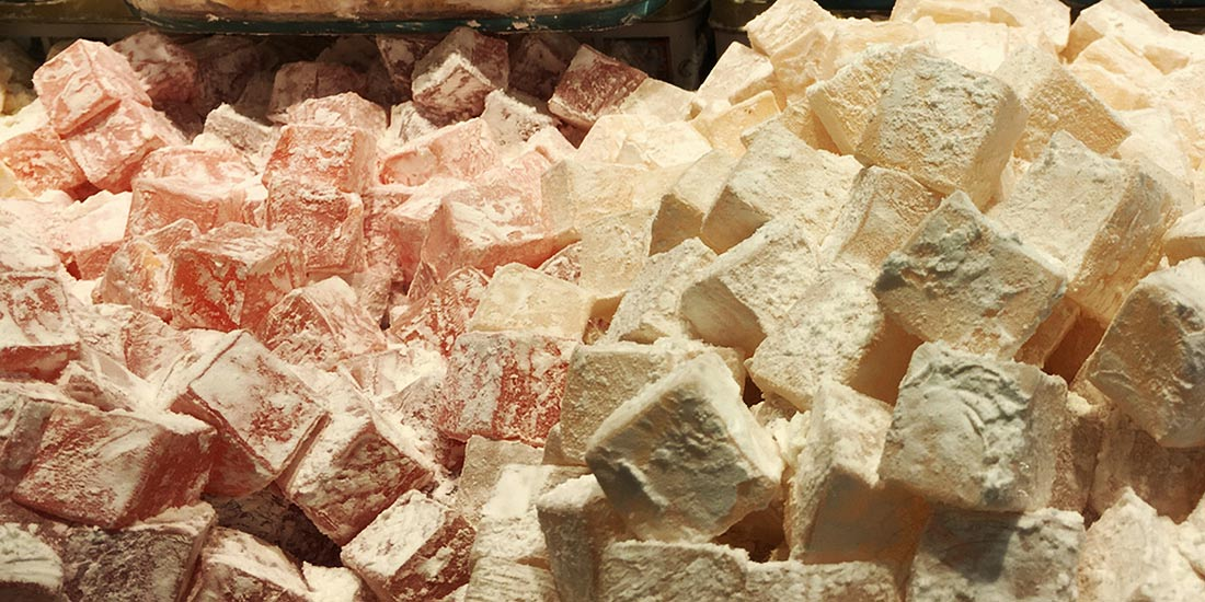 Squares of Bulgarian Delight are coated with powdered sugar for eating.