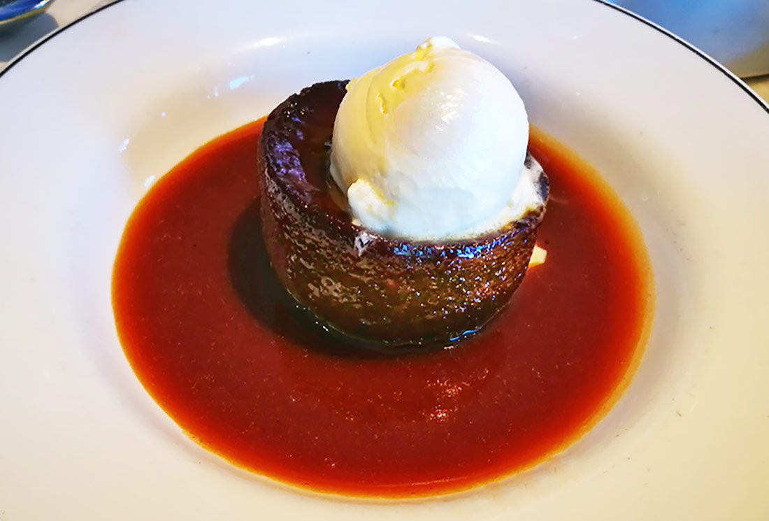 A rich, cake-like sticky toffee pudding topped with vanilla ice cream and sitting in a luscious pool of caramel sauce.