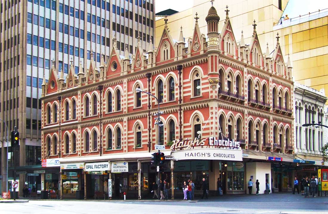 Beehive Corner in downtown Adeliade, South Australia, is home to Haigh's Chocolates, in a fanciful, neo-Gothic building with stripes and gables, spires and dentilated cornices.
