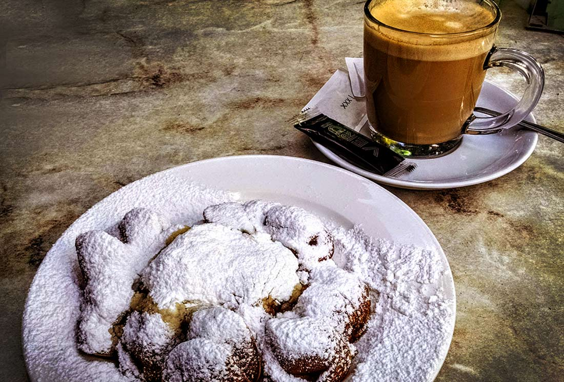 A plate of poffertjes in Amsterdam, slathered in butter and hidden under a thick coat of powdered sugar.