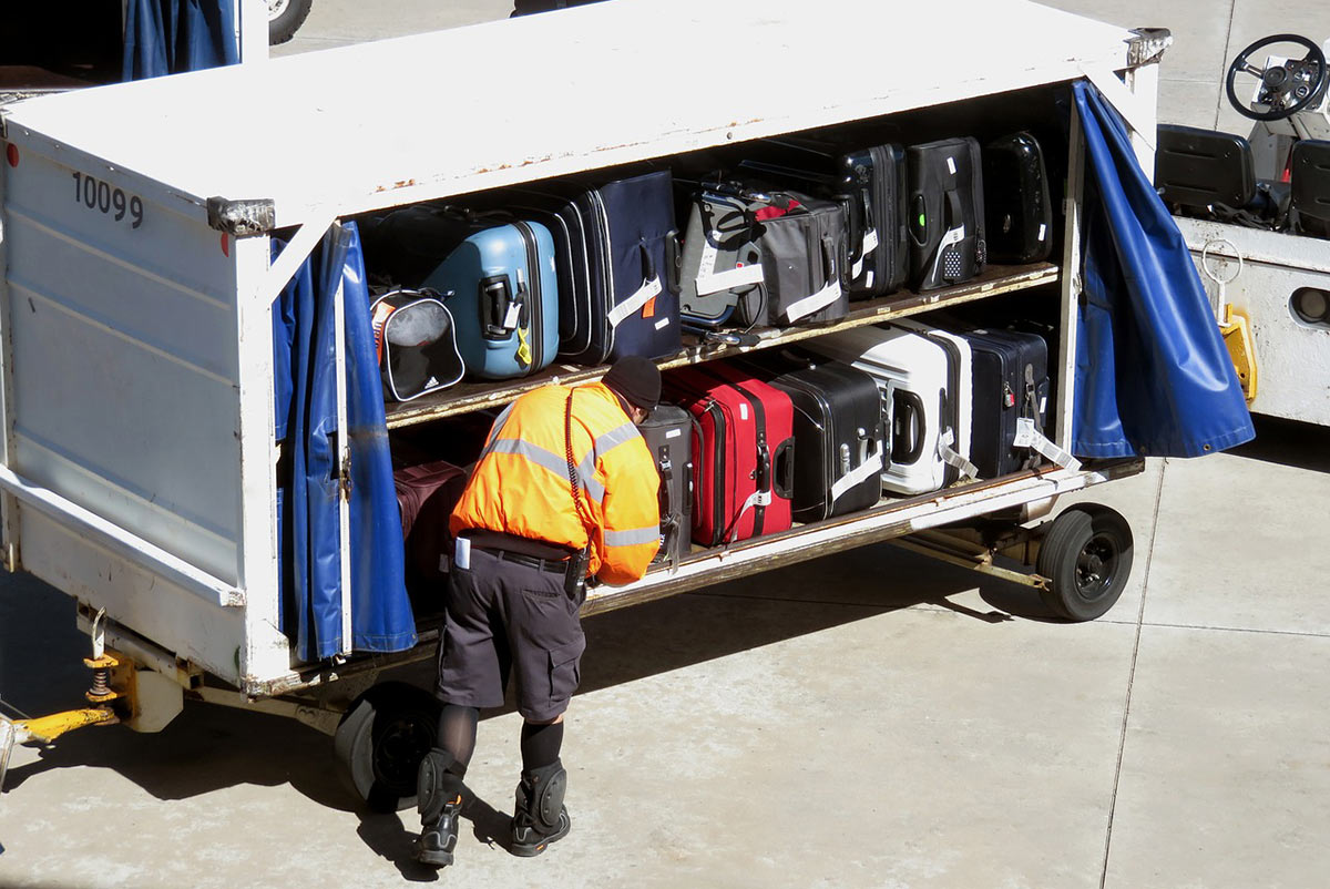 Baggage handlers have a lot of luggage to deal with for every flight, like this guy with a full airport baggage cart. Give them time to do their job.