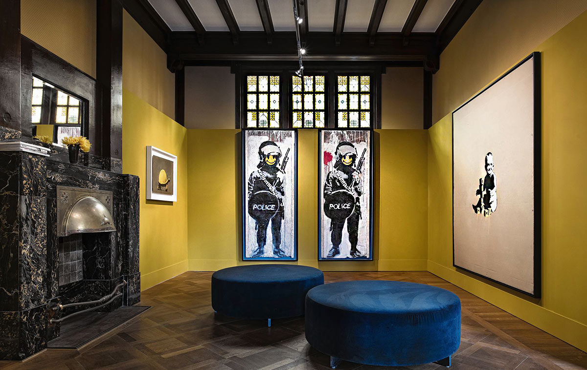 "An elegant room in the Moco Museum, with yellow walls and a heavily beamed ceiling, showing two ""Stormtrooper"" paintings by Banksy on one wall, below vintage beveled glass windows."