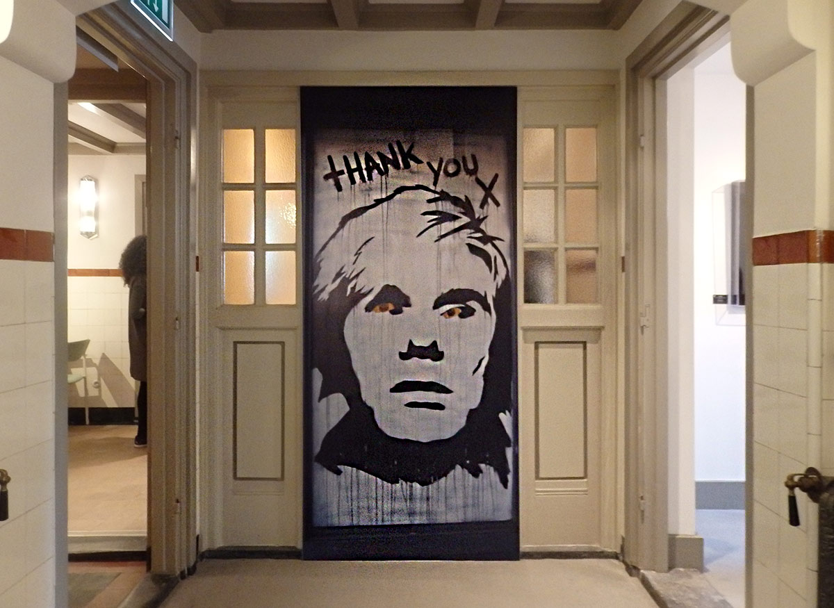 A large black-and-white self portrait of Andy Warhol sits against an elegant glass and wainscoting wall at Moco Museum, Amsterdam