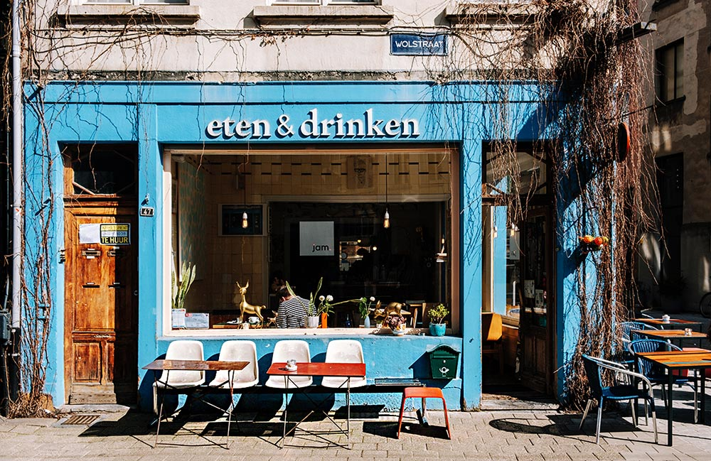 Eten & Drinken, a blue-walled cafe in Antwerp, with four chairs on the sidewalk, a place to sit and relax with your morning coffee.