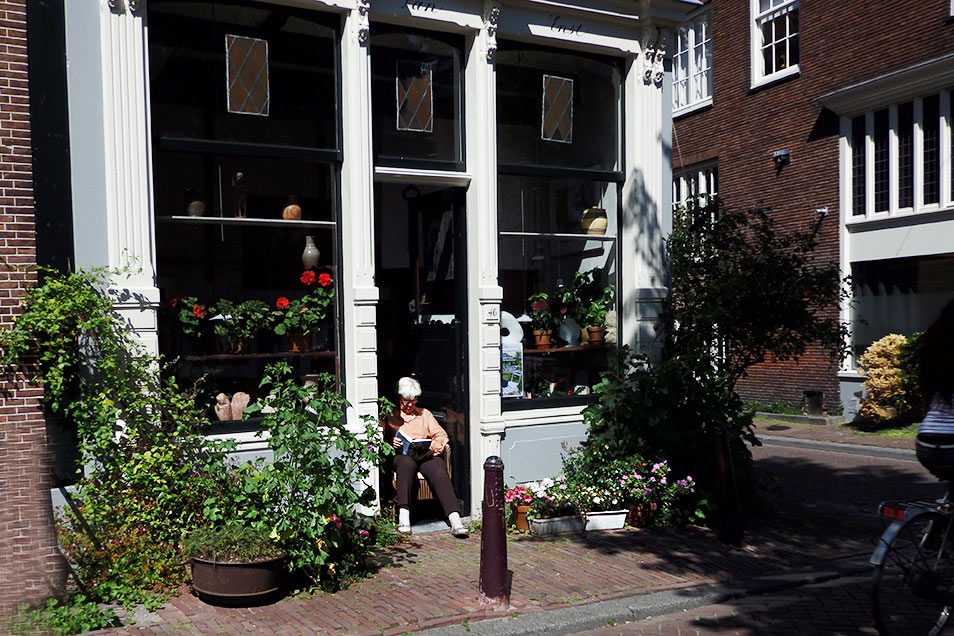 In a narrow street in Amsterdam's Jordaan, a woman sits in her open front doorway, reading a book and enjoying the sun.