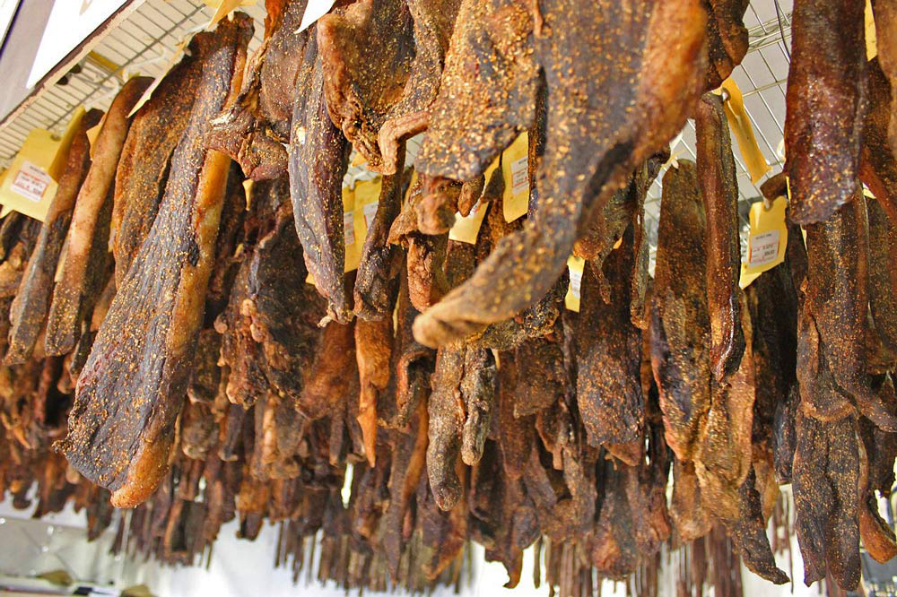 Long strips on biltong, dried meat, like beef jerky, hanging in a shop in South Africa.