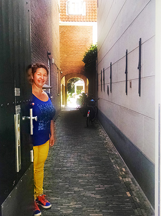 Our Eating Europe Amsterdam guide, Mirka, opens the door to invite us to visit a hofje.