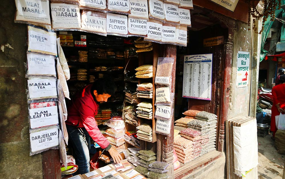 A tiny, open-front shop in Kathmandu, the size of a newspaper kiosk, selling dozens of packages of different spices and teas, including cumin, garam masala, saffron flower, and ilam leaf tea.