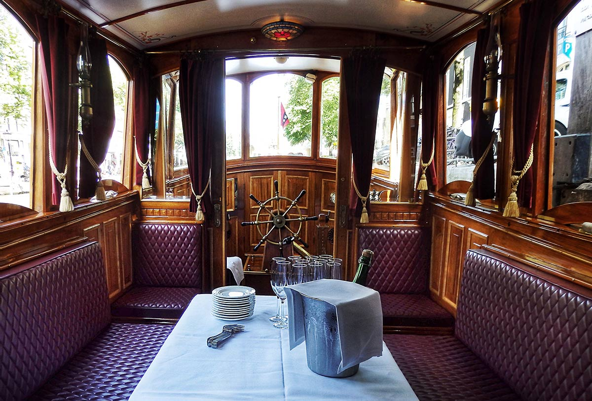 "The interior of the 1909 saloon boat ""Tourist"" glows with polished brass and teak, maroon upholstery, marble and beveled glass. Here she is set with white linen, with cheese and a bucket of champagne awaiting her guests for the Eating Europe Amsterdam Food Tour."