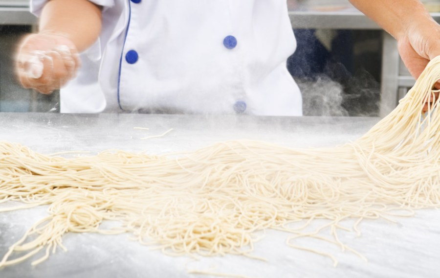 flour and noodle dough - Chef making noodles in the kitchen of cooking school.