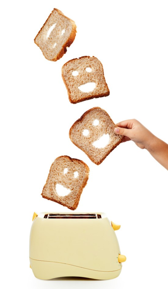 Child hand catches toast bread slices flying out of a toaster