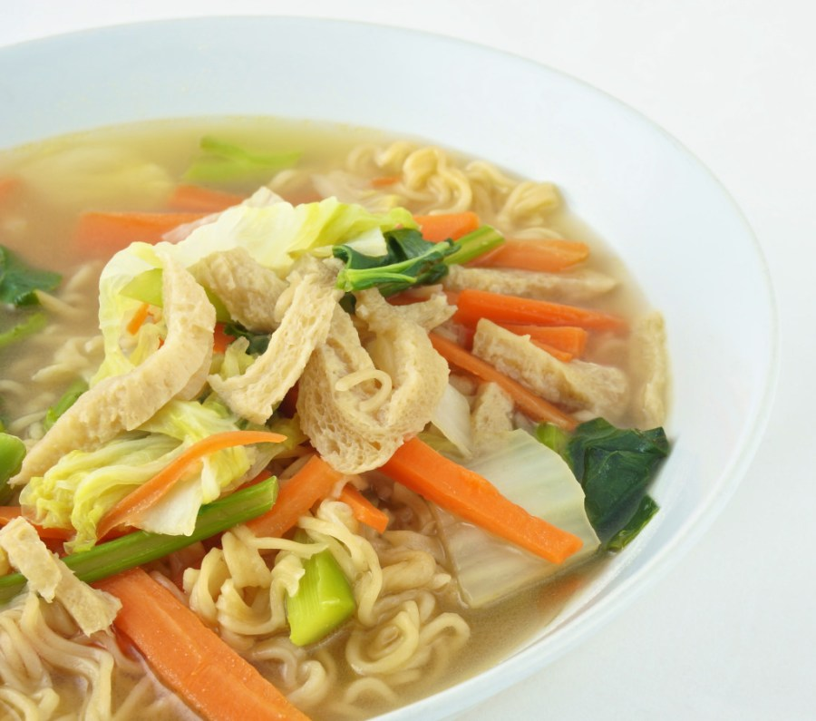 Egg noodle and clear soup vegetarian for health. It include vegan protein dry, carrot, kale and cabbage on white background.