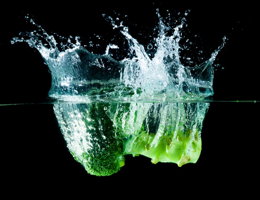 Salting the greens keeps them green - Green broccoli falling in water on white with air bubbles