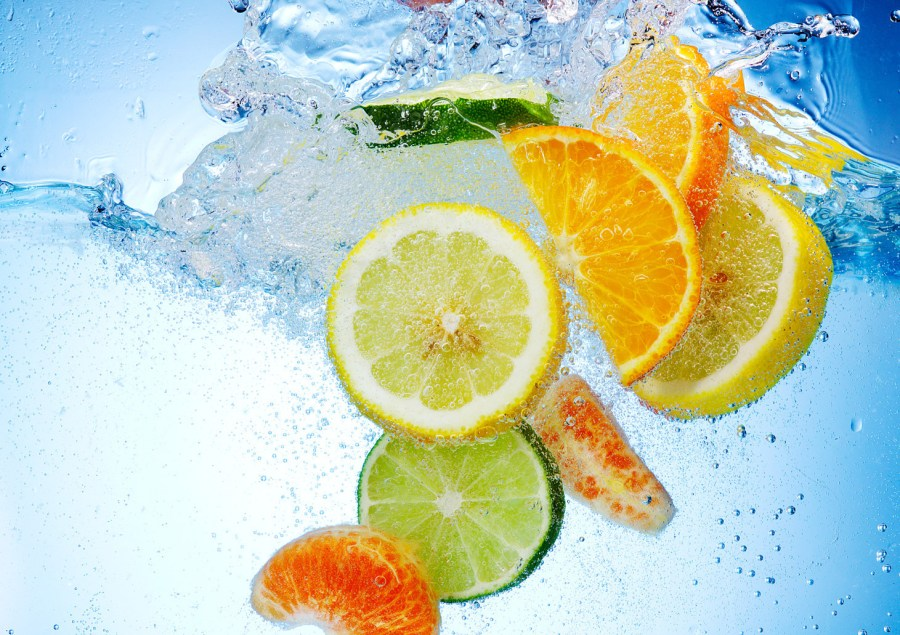 Citric acid citrus fruits - Tropical fruits are falling deeply under water with a big splash