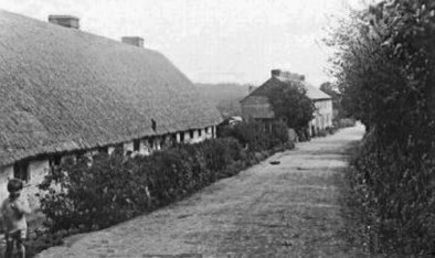 If you were church-bound from Acol [Ackholt] then the first buildings you encountered as you walked along Church Street were the old Poor House Cottages on your left. The row of six cottages built in the early 1820's with the rear of the cottages facing onto the road, and the front of the cottages overlooking their gardens. The boy on the left of the picture is believed to be Frank Harrison, whose family lived in Church Street. Beyond the cottages is Church Street Row and beyond the Row is the old main Poor House building.