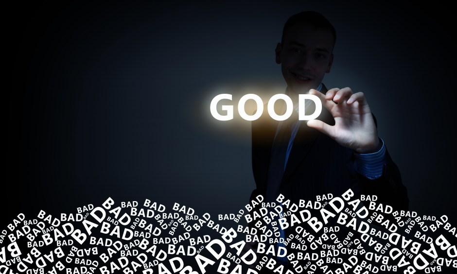 Businessman on dark background taking with fingers glowing word good