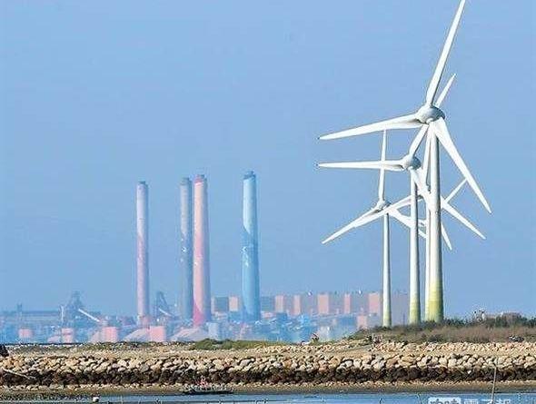 圖為位於彰化縣線西鄉的風力發電機組(右前)與台中火力發電廠(左後)。(資料照,黃世麒攝)