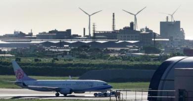 桃園觀音外海將蓋離岸風機,可會導致桃機第三跑道蓋不成,圖為桃園機場北跑道上被拖行的航機,遠方是現有的台電風機。記者鄭超文/攝影
