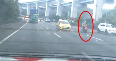 機車騎士看見前方的巡邏車,仍在高速公路內線車道穿梭車陣。記者林昭彰/翻攝