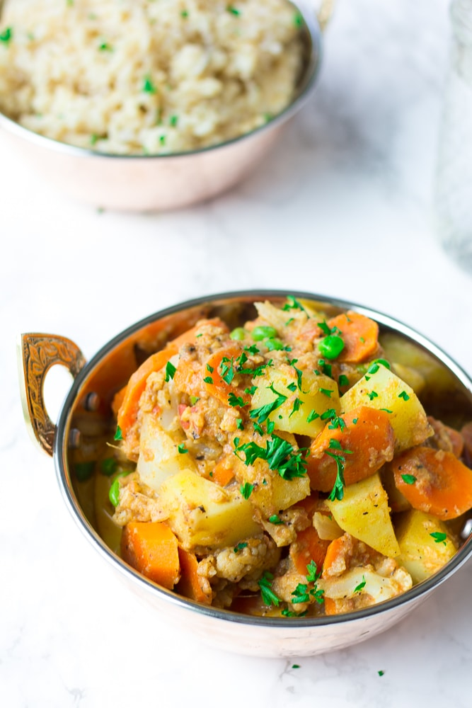 vegetable korma in a dish with rice behind it in a bowl