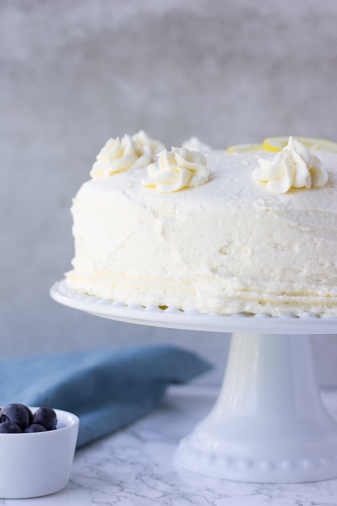 whole vegan lemon cake from the side shot with blue towel and grey background.