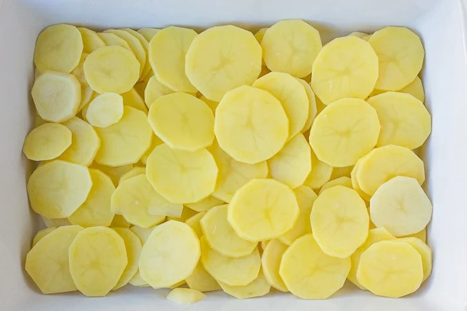 vegan scalloped potatoes, raw potatoes sliced in casserole dish